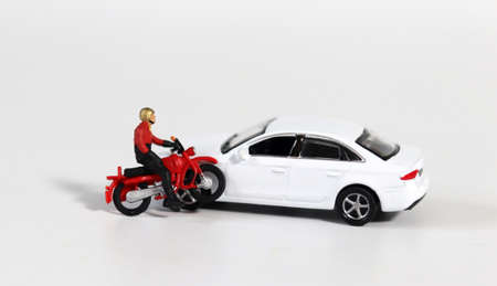 Miniature people and miniature car. A miniature motorcycle rider in front of a white miniature car. Concept about a dangerous motorcycle accident.