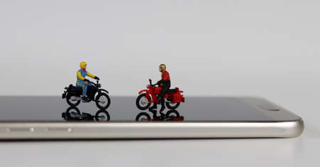 Two miniature motorcycle riders on the smartphone. Concept of delivery competition according to the increasing number of online orders.