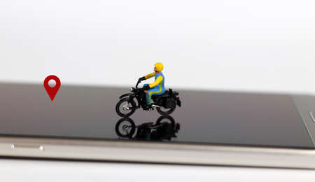 Smartphones and miniature people. A miniature motorcycle rider with a red location mark on the smartphone.