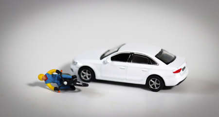 Miniature people and miniature car. A miniature motorcycle driver who fell in front of a white miniature car. Concept about a dangerous motorcycle accident. 版權商用圖片