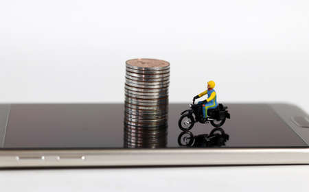 Smartphones and miniature people. A miniature motorcycle rider and coins on the smartphone.