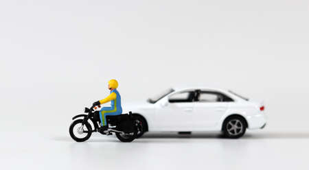 A miniature driver wearing a helmet next to a white miniature car and riding a motorcycle. Miniature people and miniature car.