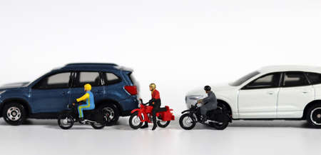 Concept about the dangers of speeding motorcycles. Miniature people and miniature car. Miniature motorcycle messenger between miniature cars.