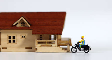 A miniature delivery man riding a motorcycle in front of the door of a miniature house. Miniature people and miniature house.