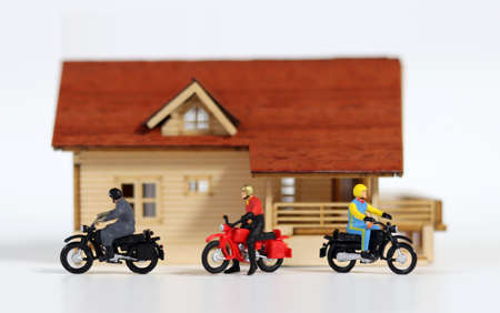 Three miniature motorcycle riders in front of a miniature house. Miniature people and miniature house.