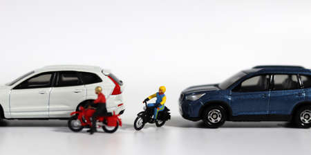 Miniature people and miniature car. A motorcycle rider who forcefully intervenes between two cars. Concept on the importance of safe driving and the risk of accidents. 版權商用圖片