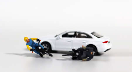 Miniature people and miniature car. White cars and fallen motorcycle drivers. Concept about the dangers of speeding motorcycles. 版權商用圖片