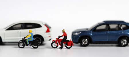 Miniature motorcycle messenger between miniature cars. Miniature people and miniature car. 版權商用圖片