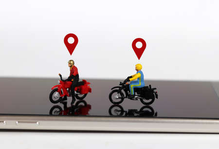 Smartphones and miniature people. Two miniature motorcycle riders with two red location mark on the smartphone.