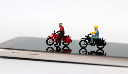Two miniature motorcycle riders on the smartphone. Concept about useful online delivery.