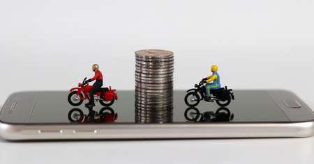 Smartphones and miniature people. Two miniature motorcycle riders and coins on the smartphone.