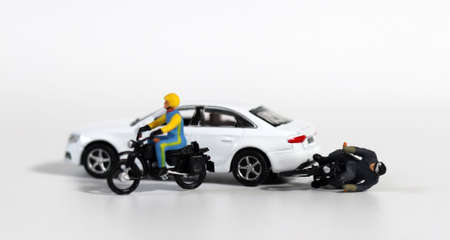 Miniature people and miniature car. White cars and fallen motorcycle riders. Concept about the dangers of speeding motorcycles. 版權商用圖片