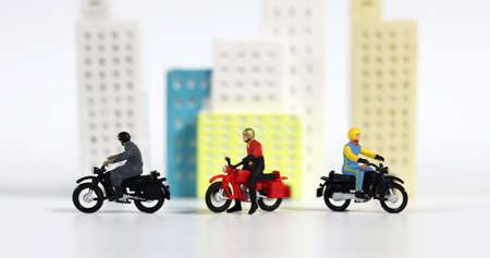 Three miniature motorcycle riders in front of a miniature building. Miniature people and miniature building.