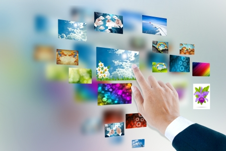 men hand using touch screen interface with pictures in frames photo