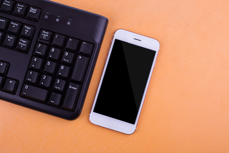 qwerty: Smart phones with a QWERTY keyboard and a battery charger. Stock Photo