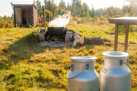 Two milk cans in the foreground and a burning kettle in the background. A real genuine landscape. Stock Photo
