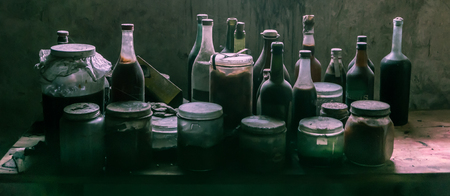 Real old glass bottles and jars with strange content. Covered in dust and spiderwebs.