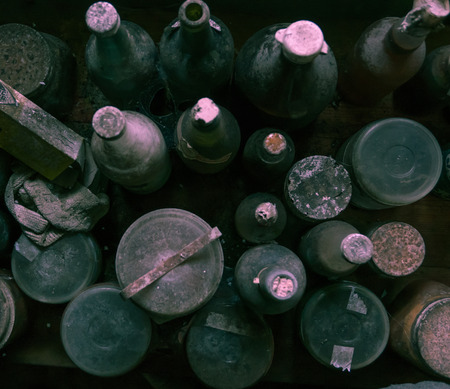 Birds view of old dusty and spider web covered bottles.