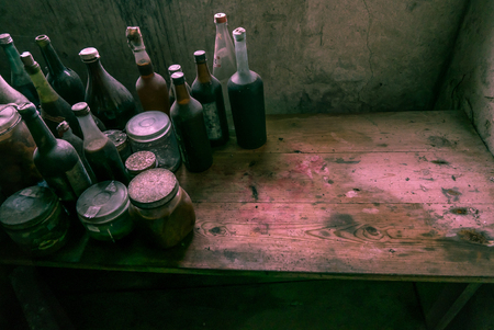 An old and stained bench full of glass bottles. Plenty of room for text. This must be an old witch's kitchen.