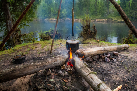 A hanging pot over the fire with slowly streaming water in the background.