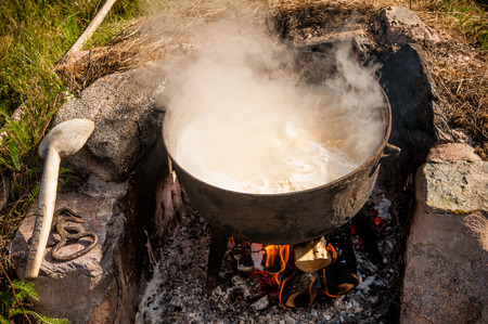 Making cheese the old way. Looks like a witchs kettle boiling with unidentifiable content.