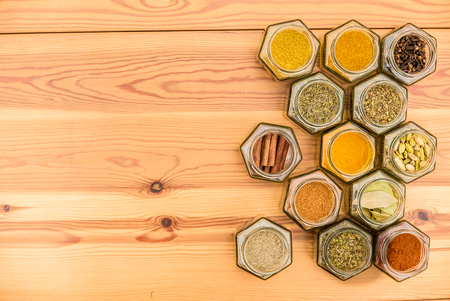 Colorful herbs and spices in hexagonal glass jars with room for text on wooden background. Horizontal alignment. Stock Photo