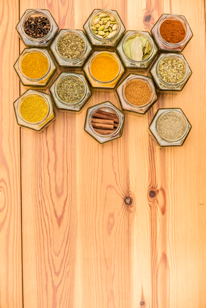 Colorful herbs and spices in hexagonal glass jars with room for text on wooden background. Vertical standing alignment. Stock Photo