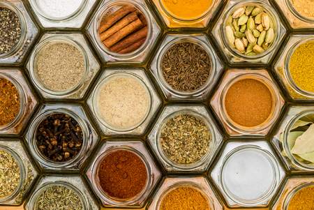 Colorful herbs and spices in hexagonal glass jars. Natural colors and top view. Horizontal picture. Stock fotó