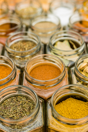 Many jars of tasty colorful seasoning herbs and spices. Vertical standing photo. Stock Photo