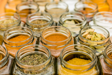 Many jars of tasty seasoning herbs and spices. Horizontal photo.