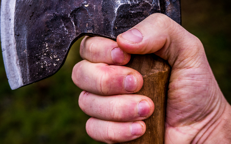 Closeup of a hand holding an axe in a firm grip. Symbolises determination, manliness, strength and vigor. Stock Photo