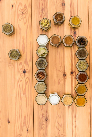 Colorful spices surround space for text. A few herb jars are spread out around the frame. Vertical standing picture. Stock Photo