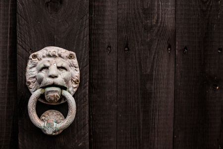 A dark black wooden background with a lion shaped door knocker on left side and room for text on right side. Stock Photo