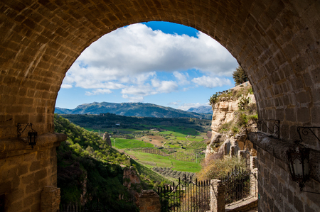 A beautiful landscape seen through an arch in Ronda, Spain