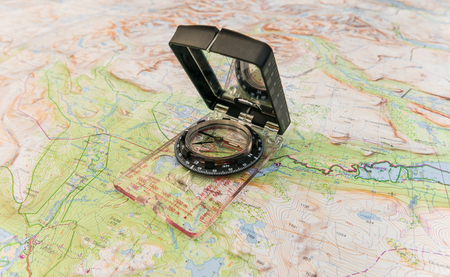 For finding direction in life and the wilderness a compass and map is necessary. Stock Photo
