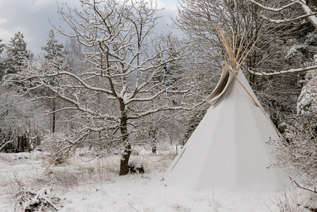 A snowy winter landscape with a tipi tent