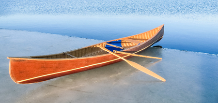 A very motivated person has carried their canoe to the edge of the ice in wait of spring.