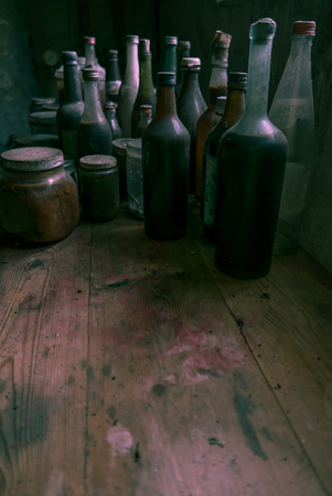 Glass bottles on a stained wooden bench with room for text below underneath.