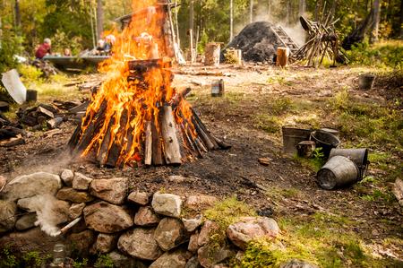 Een hete brandende teerstapel met een houtskoolput op de achtergrond. Let op de rookpijp waar de teer in het onderliggende blik druppelt.