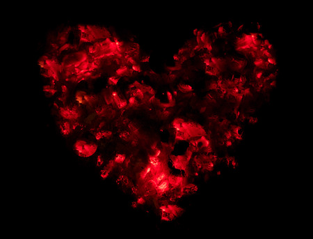 Love symbolised by a red passionate heart made of embers. Stock Photo