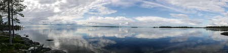 A panorama background with reflective water, a dramatic sky and islands.