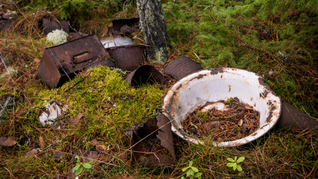 Old metallic waste trash has been dumped in the forest long ago to rust away. Stock Photo
