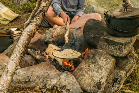 Using a frying pan to bake some bread outdoors over a burning campfire. Stock Photo