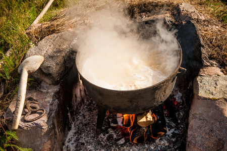 Making cheese the old way. Looks like a witchs cauldron boiling with unidentifiable content. Stock Photo