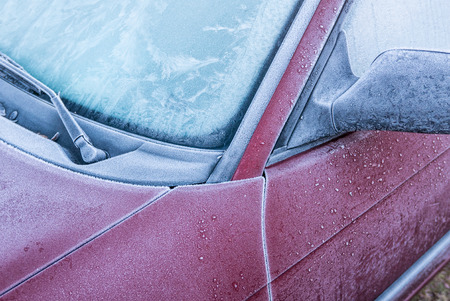 A red car covered in frost and ice on a cold winter morning when going to work. Stock Photo