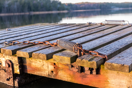 Mooring devices in the form of metallic rusty springs on wooden pier with blurred sea in the background.
