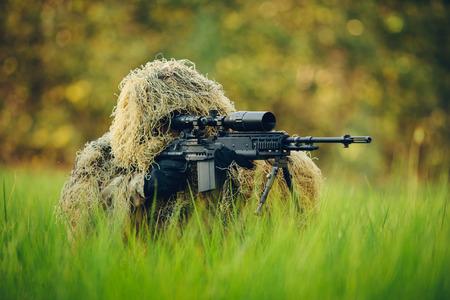 fusil de chasse: Sniper dans l'herbe en regardant à travers la portée