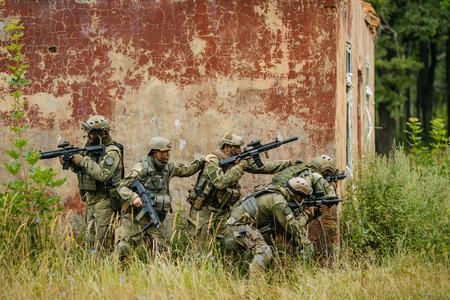 カバーの後ろから敵を攻撃する兵士のチーム 写真素材