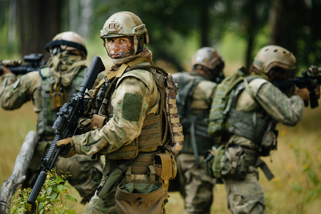 military uniform: team of soldiers engaged in the exploration of the forest