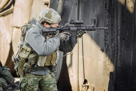 bulletproof vest: military soldier shooting an assault rifle Stock Photo